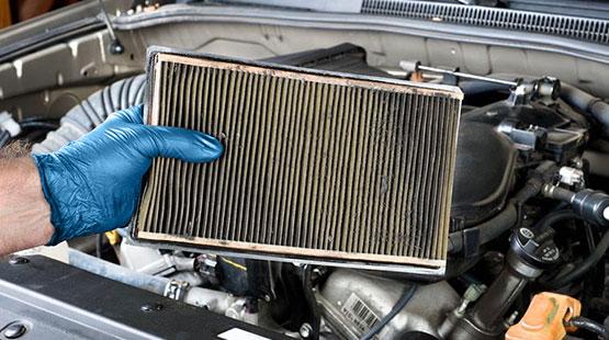Mecánico sosteniendo un filtro de cabina sucio